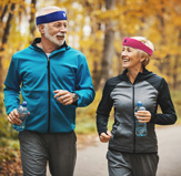 Senior man and woman jogging on road in woods